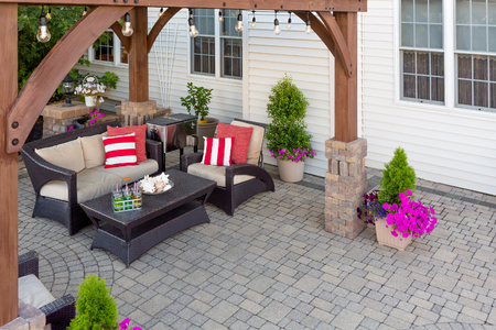 Comfortable chairs with colorful red cushions on an outdoor brick patio covered by a wooden gazebo in front of a timber clad house