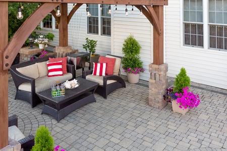 Cómodas sillas con coloridos cojines rojos en un patio de ladrillo al aire libre cubierto por una glorieta de madera en frente de una casa revestida de madera