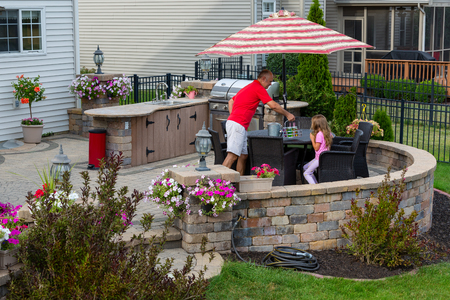 Daddy serving lemonade to his little daughter outdoors on a brick patio as she relaxes in the shade of an umbrella near an outdoor kitchen and gas barbecue in summer Banque d'images - 105145567