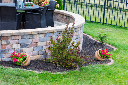 Curved round brick wall on an outdoor patio with feature flowerbed in a neat green lawn and wicker armchairs under an umbrella