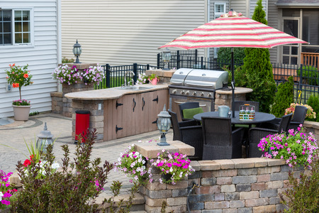 Upscale outdoor patio with kitchen area and comfortable wicker furniture in the shade of a striped umbrella surrounded by summer flowers Banque d'images