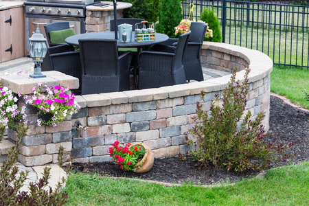 Comfortable seating on a raised exterior patio with curved round brick wall set in a neat manicured backyard for outdoor living Banque d'images - 105685186