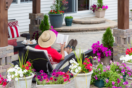 Man in a straw sunhat sitting on a recliner chair relaxing reading on an outdoor patio viewed across colorful potted summer flowers on the wall Stockfoto