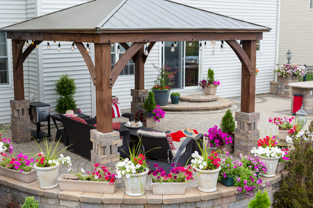 Colorful summer flowers on a curved exterior patio with covered gazebo and comfortable furniture in an upscale backyard Stock Photo