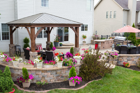 Colorful exterior curved patio with summer flowers and comfortable wicker armchairs under a covered wooden gazebo with aluminum roof in a neat upscale backyard Banque d'images - 105684655