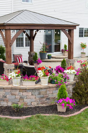 Curved brick exterior patio with a colourful array of potted summer flowers on the wall and a wooden gazebo for healthy outdoor living