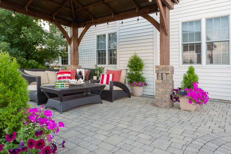 Brussel block design pavers on an exterior patio and summer living space with a covered gazebo, colorful petunias and comfortable seating Stock Photo