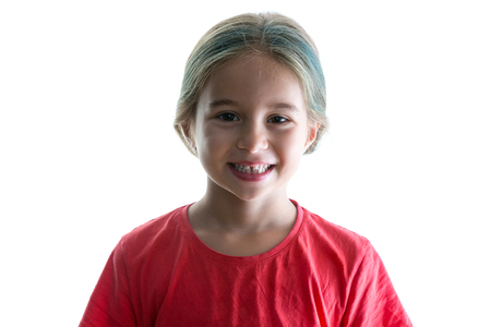 Cute little girl with a cheerful playful grin and colourful dyed highlights in her long blond hair smiling happily at the camera isolated on white