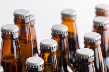 Low angle shallow dof view of the necks and caps of full brown bottles of craft beer arranged in rows on a white background