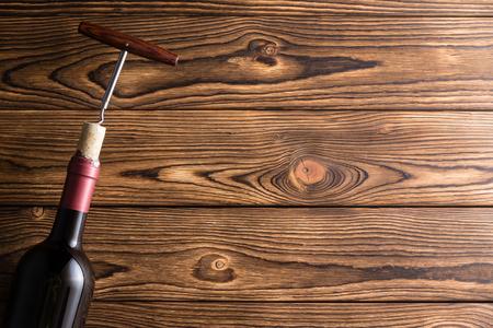 Bottle of red wine with corkscrew against dark wooden background