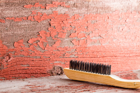 Wooden cleaning brush against red ragged painted wall with copy space