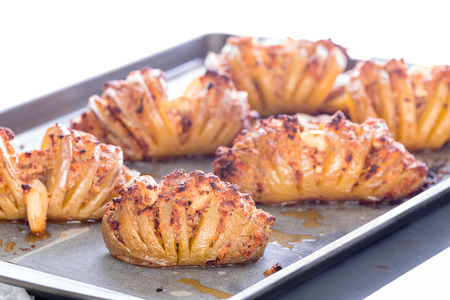 Tasty freshly baked sliced tornado or roly poly potatoes with savory filling on a baking tray in a low angle view