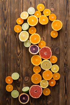 Juicy healthy ripe halved citrus fruit in an S-shape on a wooden background with decorative woodgrain texture in a close up overhead view