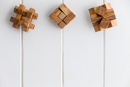 Three geometric interlocked wooden puzzles arranged in a neat line as a top border on white painted wood boards with copy space Фото со стока