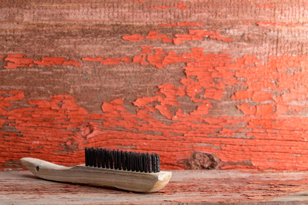 Wooden cleaning brush against red old rugged painted wall