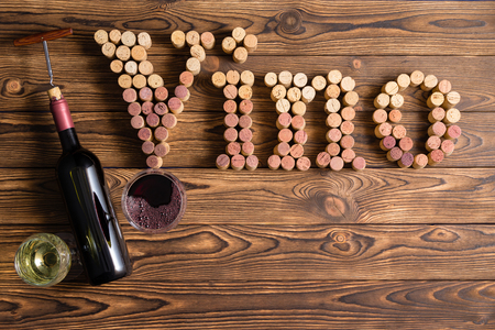 Vino lettering made of corks with bottle and glasses against wooden background
