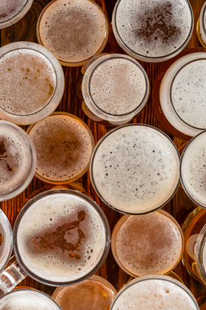 An variety of full, frothy beer glasses and sizes on a bar bench top. Stockfoto