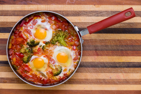 Tasty spicy traditional shakshuka with broccoli and poached eggs on a laminated wooden board served in a frying pan viewed from above with copy space Banque d'images - 105683906