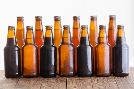 Double row of assorted chilled homemade unlabelled bottles of craft beers of a variety of types in different shaped bottles suitable for advertising or a promotion