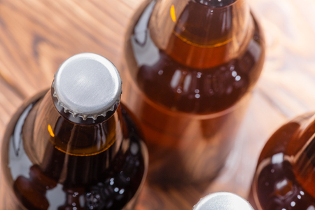 Close up high angle view of unlabelled bottles of craft beer with focus to the cap on a single bottle over a wood background Stockfoto
