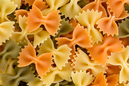 Close up of multicolored tricolor dried uncooked farfalle Italian pasta also known as bow tie or butterfly pasta, in a full frame background texture for healthy Mediterranean cuisine 免版税图像
