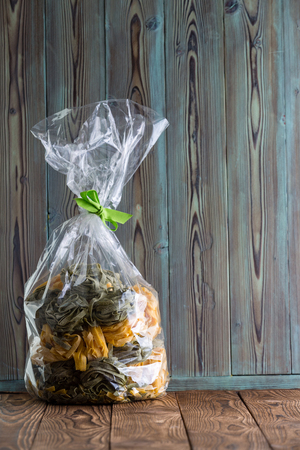 Clear plastic bag of homemade fresh fettuccine Italian pasta with both plain egg and green spinach varieties on a rustic wood background with copy space