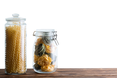 Two storage jars filled with fresh dried pastas with homemade fettuccine and fusilli bucati lunghi long spirals against a white background with copy space 写真素材