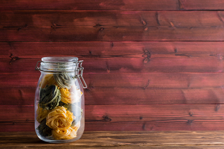 Glass masons jar filled with fettuccine pasta on a wooden table against a rustic wood plank background with copy space
