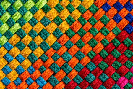 Background completely covered by diagonally angled rainbow colored interweaving threads of stitched fabric Banque d'images