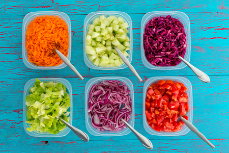 Individual dishes of colorful assorted freshly sliced vegetables with spoons viewed overhead on a blue woof background for a healthy diet