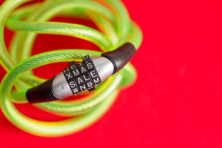 Plastic covered bike cable and combination lock with the code - Xmas Sale - over a festive red background with copy space for seasonal promotions and advertising