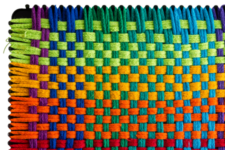 Repeating pattern of multicolored embroidery with threads looped around knobs at edges of plastic mat Standard-Bild