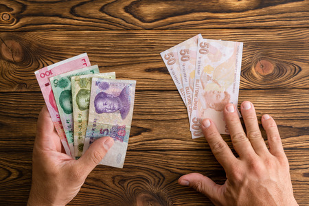 Man using Chinese Yuan to pay instead of Turkish lira in a concept of foreign trade and currency exchange, crisis, devaluation, and economic policy