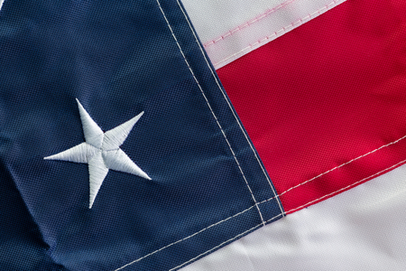 American national flag folded to show a single star representing one of the original 13 colonies and red, blue and white stripes in a full frame background view Stock Photo