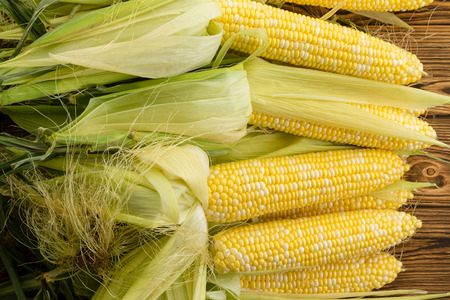 Pile of fresh yellow sweetcorn on the cob with the leaves peeled back to exposed the kernels over a wooden table at an organic farmers market
