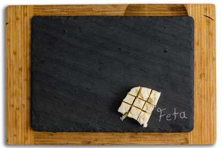Diced serving of creamy traditional Greek feta cheese made from goat and sheep milk on slate with copy space over a wooden board