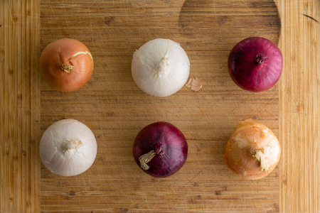 Six fresh whole unpeeled red, brown and white onions neatly arranged in two alternating rows on a bamboo cutting board in a flat lay still life Banco de Imagens