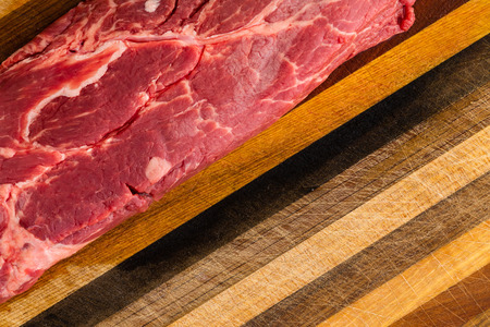 Close up on fatty red uncooked steak sitting on scratched wooden cutting board