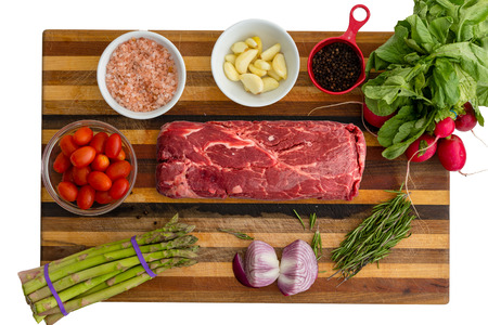 Overhead view of red meat and asparagus next to basil and small bowls of seasoning sitting on top of wooden cutting board Фото со стока