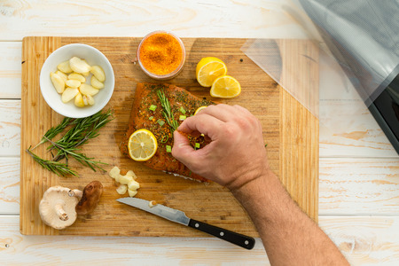 Unidentified man placing rosemary herbs on fish fillet next to small bowl of garlic cloves and knife sitting on cutting board