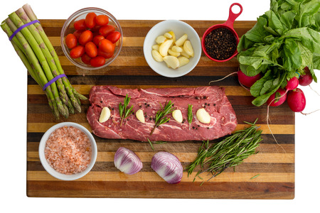 Overhead view of seasoned meat next to vegetables including tomatoes and basil leaves on top of cutting board