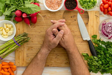 Man resting hands on wooden cutting board bordered by multiple vegetables including green pepper and carrots next to small bowls of spices