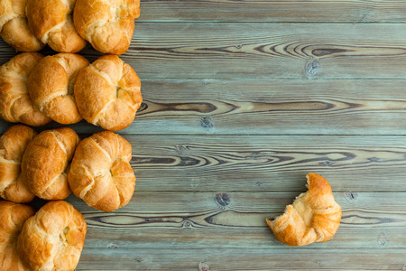 Rows of freshly baked croissants in a side border with a single half eaten croissant to the side on rustic stained wood Фото со стока