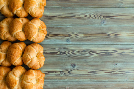 Tasty fresh golden flaky croissants border to the side on rustic wooden boards