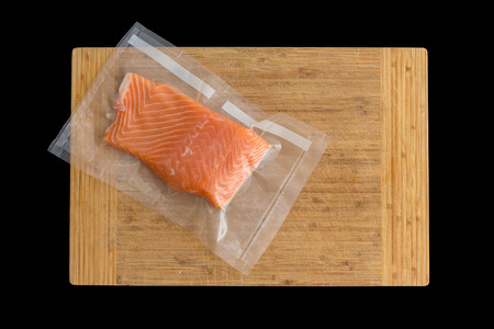 Piece of gourmet oceanic salmon vacuum packed in clear plastic Фото со стока