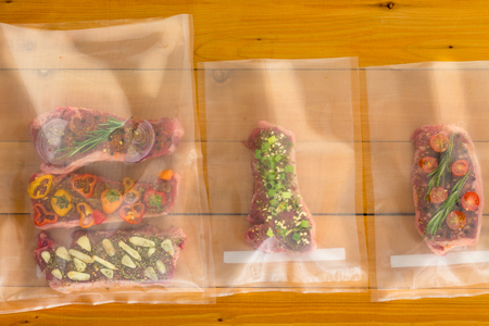 Vacuum packed flat iron steaks for freezing ready for sous-vide cooking with three different savory seasonings on a wooden board