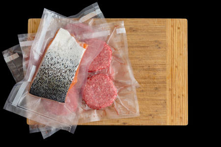 Salmon and beef burger patties vacuum packed for sous-vide cooking to be immersed in water