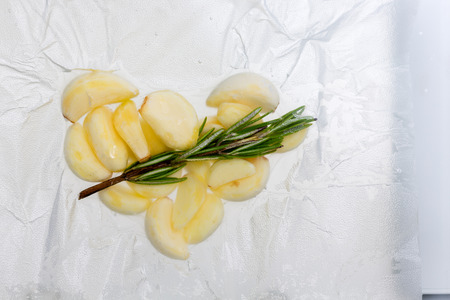 Fresh whole garlic cloves with rosemary cooking immersed in water in a plastic sealed bag in a sous-vide