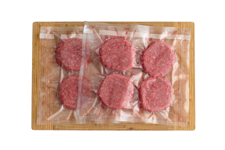 Isolated fresh beef burger patties in a vacuum pack ready to be frozen for sous-vide cuisine Фото со стока