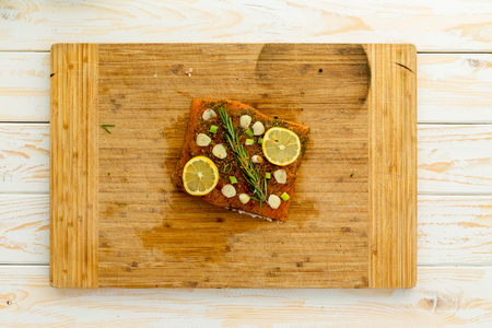 Slice of fish fillet covered in seasoning and herbs in center of wooden cutting board sitting on top of white wooden table Фото со стока